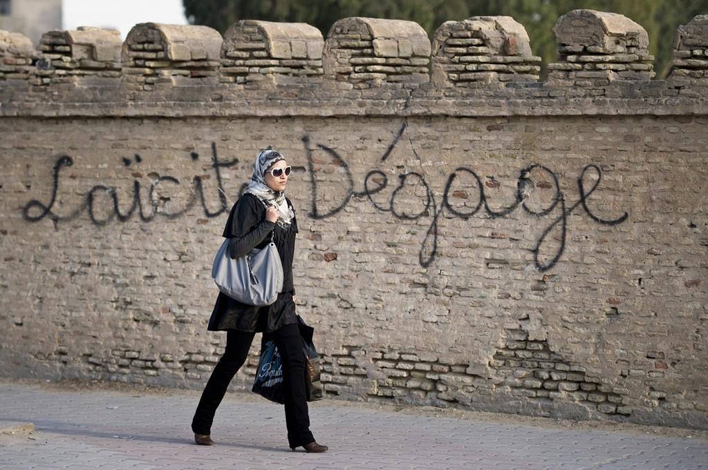Femme tunisienne qui passe devant un graffiti contre la laïcité par Ezequiel Scagnetti. 2011. (CC BY-NC-ND 2.0)